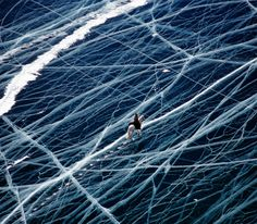 Horse and rider crossing the frozen Lake Baikal, Siberia. Photo by Matthieu Paley